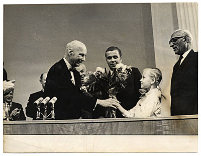 Rockwell Kent receiving flowers from a young girl during the award of the Lenin Peace Prize