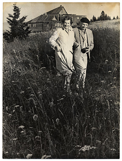 [Rockwell and Sally Kent walking near a village in the USSR]