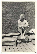 [Rockwell Kent sitting on a dock ]