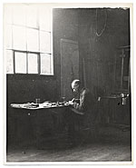 Rockwell Kent working at a desk