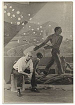 Rockwell Kent seated with his mural for the Worlds Fair