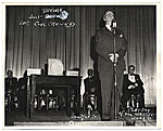 Rockwell Kent on stage in front of a microphone