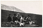 Rockwell Kent sitting on a hillside with a group of natives in Greenland