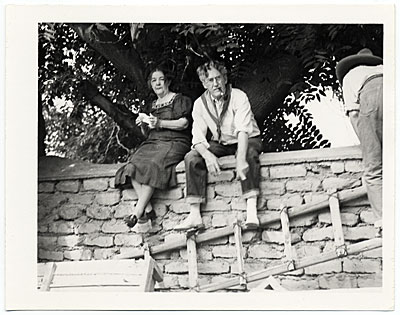 [John and Dolly Sloan seated on a wall at their Santa Fe ranch]