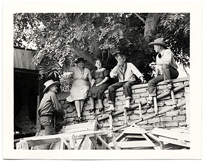 [Dolly and John Sloan and friends sitting on a wall at the Sloan's Santa Fe Ranch]