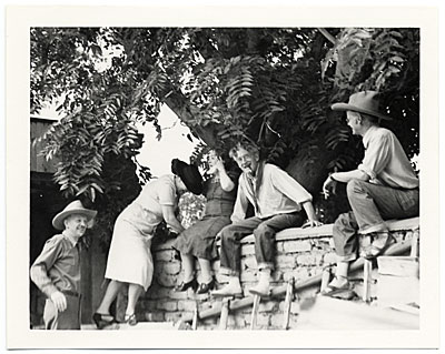 John and Dolly Sloan and friends sitting on a wall at Sloans Santa Fe Ranch
