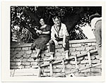 John and Dolly Sloan seated on a wall at their Santa Fe ranch
