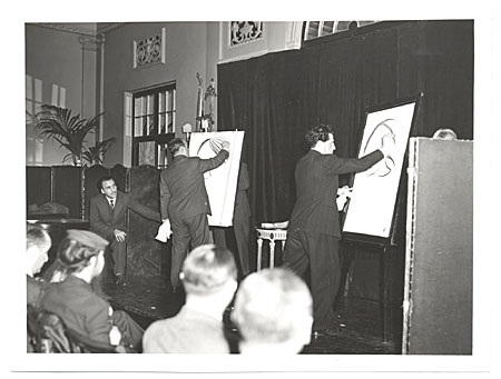 Abril Lamarque watching two caricaturists on stage