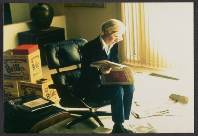 Andy Warhol reading a newspaper