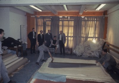 Michael Fried, Marcella Brenner, Clement Greenberg and others looking at unrolled Morris Louis canvases at Santini Bros. warehouse
