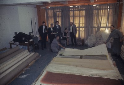 Michael Fried, Marcella Brenner, Clement Greenberg and others looking at unrolled Morris Louis canvas at Santini Bros. warehouse
