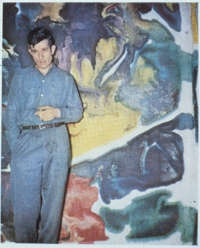 [Morris Louis standing in front of Untitled]