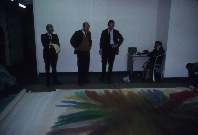 [Clement Greenberg, Michael Fried, and two unidentified people viewing an unrolled Morris Louis canvas at Santini Bros. warehouse]