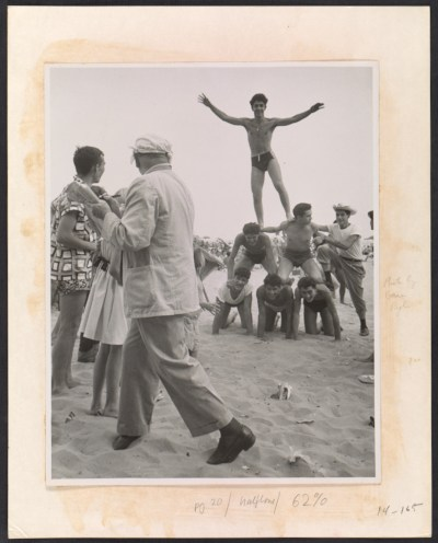 Reginald Marsh sketching men building a human pyramid on the beach