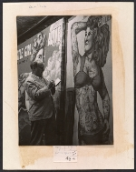 Reginald Marsh sketching a poster of a tattooed woman