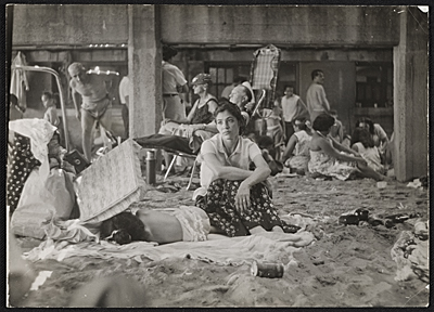 A woman and sleeping child at Coney Island