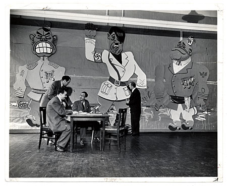 [Art Students League faculty seated around a table in front of a mural]