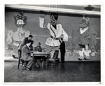 Art Students League faculty seated around a table in front of a mural