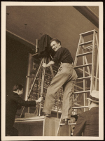 Nickolas Muray standing on a ladder at a photography set