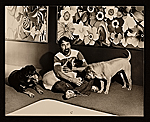 [Lowell Nesbitt sitting with his dogs in front of his artwork]