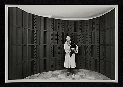 Louise Nevelson with cat in front of a black wall construction