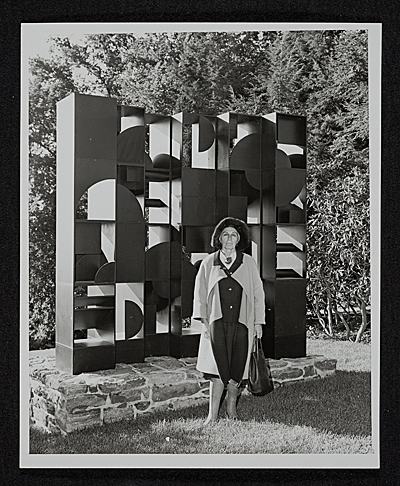 Louise Nevelson standing in front of her artwork at Pocantico Hills