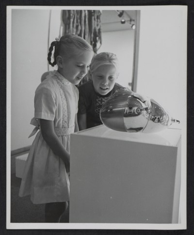 Two girls inspecting an item in the Objects: U.S.A. exhibit