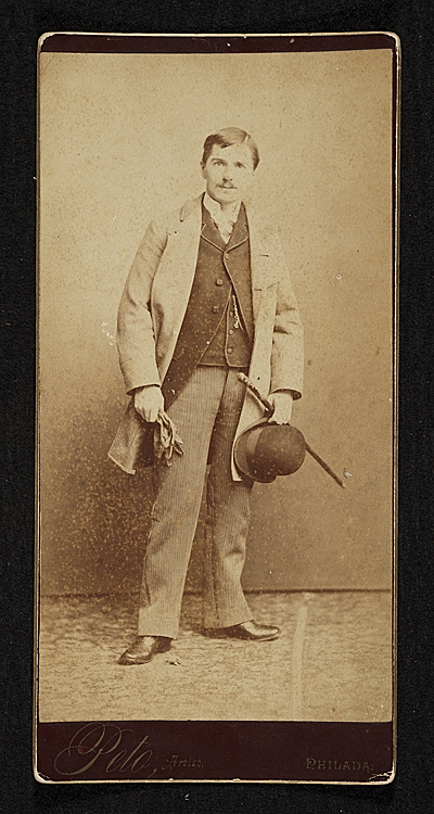 John Frederick Peto standing, holding a bowler hat