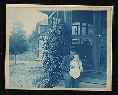 John Frederick Peto on the porch of his home in Island Heights holding his daughter Helen