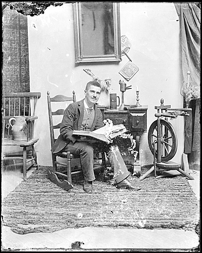John F. Peto in a rocking chair, holding an open book
