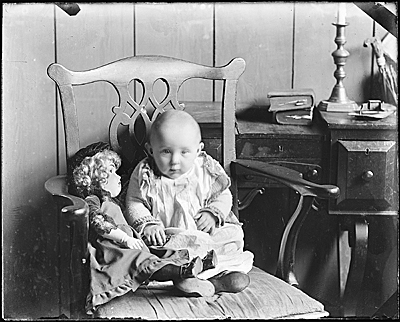 Baby Helen Peto in chair with doll