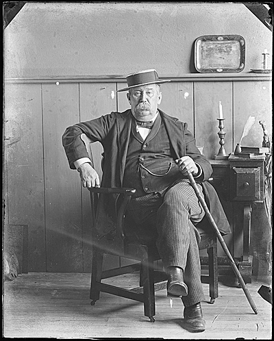 Thomas Hope Peto seated, indoors with cane