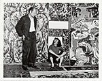 Jackson Pollock and Lee Krasner in front of his work