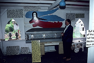 Jan Rosenak standing next to Howard Finsters casket at Paradise Gardens