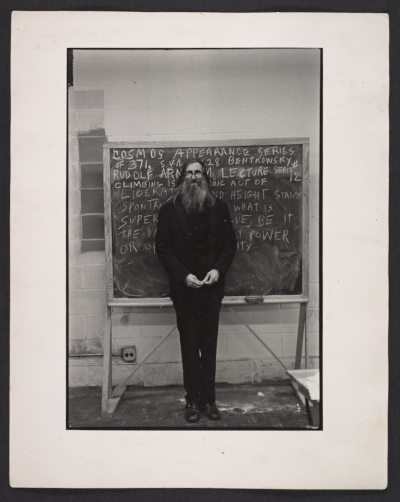 "Photo shows Cosmos standing in front of a blackboard which reads ""Cosmos appearance series #371..."""