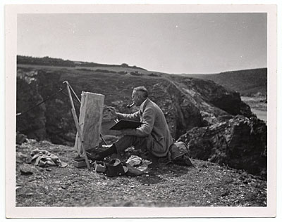 W.E. Schofield painting on the top of a hill.