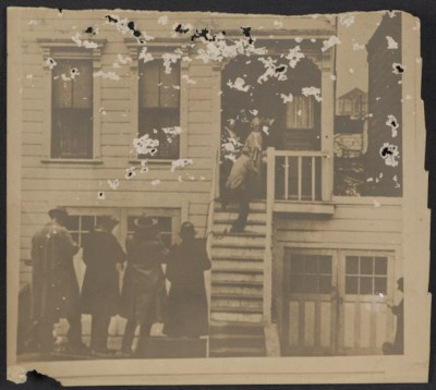 A photomechanical reproduction of a photograph showing Mrs. Mary Mooney on her porch surrounded by reporters