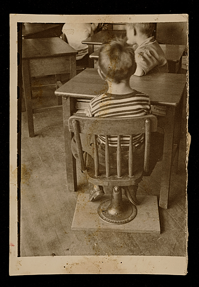 Source material for Tribute to the American Working People.  A boy seated in a chair