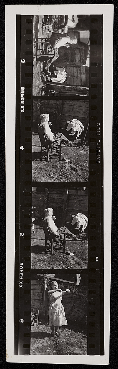 Source material for Tribute to the American Working People.  Man seated in chair and woman posing as if hanging clothes on a line