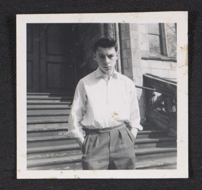 Unidentified teenage boy on the steps of a building
