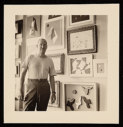 [Charles Green Shaw in his apartment with his paintings]