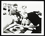 Emiliano Sorini, Irwin Hollander, June Wayne and Emerson Woelffer inspecting one of Woelffers lithographs