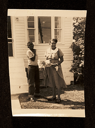 [Bob Thompson (14 years old) and his mother Bessie on their side lawn after his sister Phyllis' wedding]