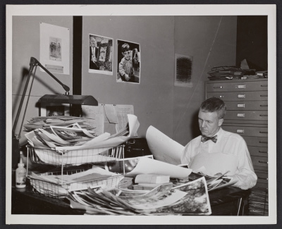 [Paul Vanderbilt, head of photo collection section, examines photos]