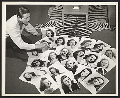 Alberto Vargas with photographs of models for the Jayhawker Annual at Kansas University