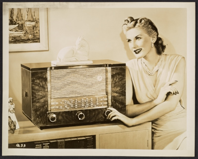 An advertising photograph featuring a model posing with a radio designed by John Vassos