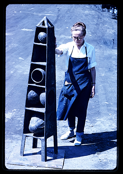 Ruth Vollmer standing next to one of her unidentified sculptures