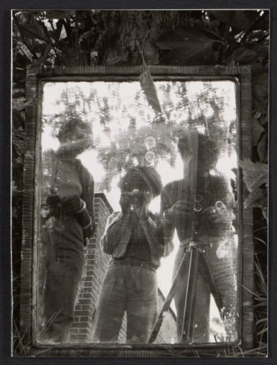 Three people reflected in a mirror.