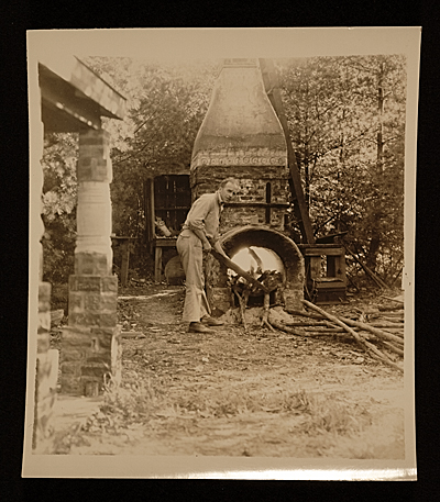 [Carl Walters feeding fire of wood kiln]