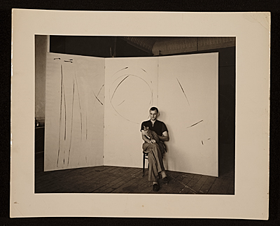 Hugo Weber with cat, sitting on a stool in front of a painting in his Chicago studio